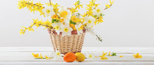 Easter Eggs With Spring Flowers On White Wooden Table