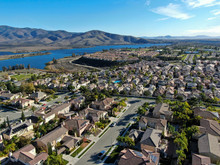 Aerial View Of Identical Residential Subdivision House With Big Lake And Mountain On The Background During Sunny Day In Chula Vista, California, USA.
