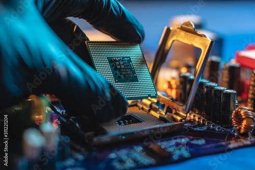 Obraz Engineer repairman holding hands CPU to insert into the socket of the motherboard. Technology hardware in the neon light - fototapety do salonu
