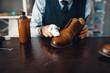 canvas print picture - Shoemaker wipes black shoe polish, footwear repair
