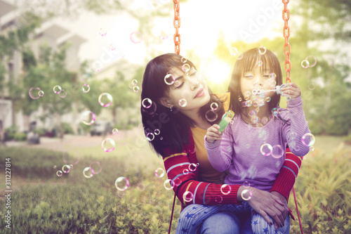 Fototapeta Mother holding her daughter while blowing bubbles obraz