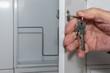 Hand von Senior öffnet weiße Briefkastenklappe mit Schlüssel