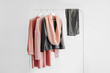 Leinwanddruck Bild - Female clothes in pastel pink and gray color on hanger on white background.  Jumper, shirt, jeans and scarf. Spring/autumn outfit. Minimal concept.