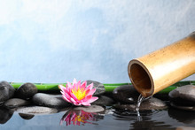 Beautiful Zen Garden With Lotus Flower And Bamboo Fountain On Light Blue Background