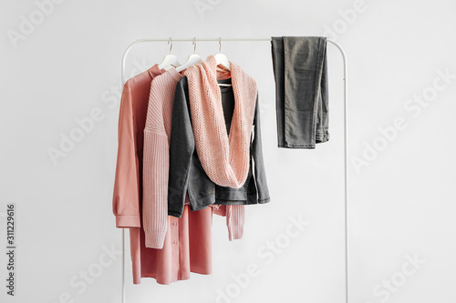 Obraz Female clothes in pastel pink and gray color on hanger on white background.  Jumper, shirt, jeans and scarf. Spring/autumn outfit. Minimal concept. - fototapety do salonu