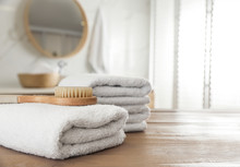 Stack Of Clean Towels And Massage Brush On Wooden Table In Bathroom. Space For Text