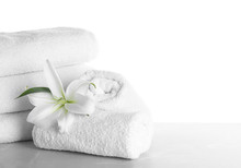 Fresh Towels And Lily Flower On Light Grey Marble Table Against White Background. Space For Text