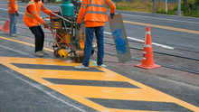 Road Workers In Reflective Vests With Thermoplastic Spray Road Marking Machine Are Working To Paint Traffic Yellow Lines On Asphalt Road With Railway Track Crossing On Street Surface,selective Focus