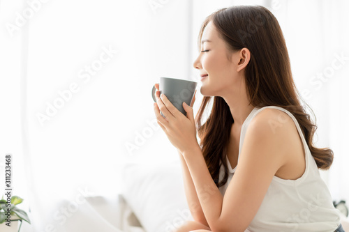 Photo Happy smiling beautiful Asian woman enjoying first morning and smelling aroma of cup of coffee tea in her bedroom