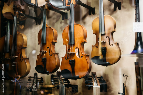 A lot of violins in a shop window selling musical instruments. - 311233668