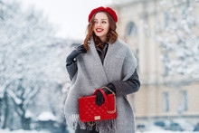 Happy Smiling Woman Enjoying Winter Holidays, Walking In Snow Covered Street Of European City. Model Wearing Beret, Grey Scarf, Coat, Gloves, With Red Quilted Bag. Copy, Empty Space For Text