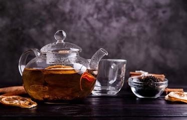 glass teapot of black tea with lemon on dark background