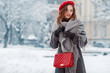 Happy smiling woman enjoying winter holidays, posing in snow covered street of European city. Model wearing beret, grey scarf, coat, gloves, with red quilted bag. Copy, empty space for text