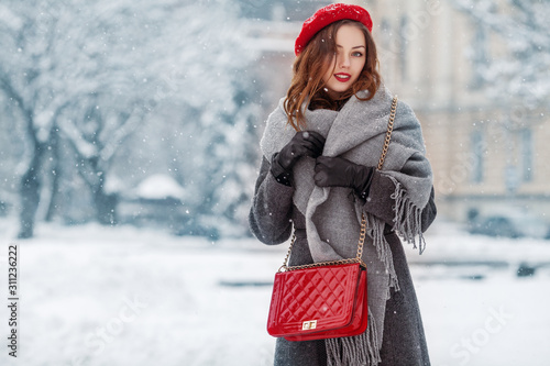 Obraz Happy smiling woman enjoying winter holidays, posing in snow covered street of European city. Model wearing beret, grey scarf, coat, gloves, with red quilted bag. Copy, empty space for text  - fototapety do salonu
