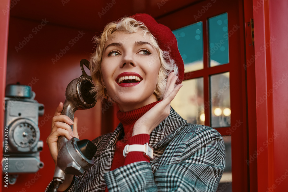 Fototapeta Fashionable happy smiling blonde woman wearing red beret, turtleneck, checkered coat, white wrist watch, talking on the retro phone, posing in red  call box. Copy, empty space for text