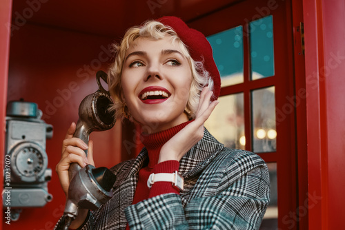 Fototapeta Fashionable happy smiling blonde woman wearing red beret, turtleneck, checkered coat, white wrist watch, talking on the retro phone, posing in red  call box. Copy, empty space for text obraz