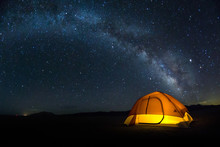 Lit Tent On The Playa Under A Bright Milky Way Arch Of Stars