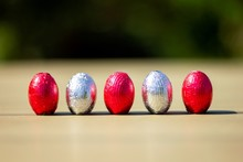 A Portrait Of Chocolate Easter Eggs Wrapped In Tin Colorful Foiln Standing Up On A Table Ready To Be Found And Eaten By Children.