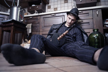Young Caucasian Man With Gun Dead From Bootleggers War During Alcolol Prohibition In USA In 1920-1930s. Concept Scene, Striped Suit, Bottles And Wine Producing Equipment.