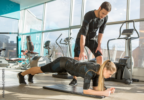 Платно Man and woman doing electro muscular stimulation training in a modern gym