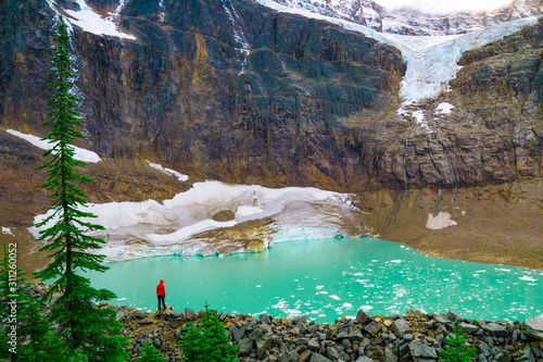 Ecologist Observing Glacier Melt Into Mountain Lake Canvas Print