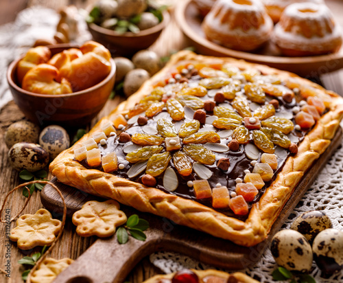 Mazurek pastry, traditional Polish Easter cake made of shortcrust pastry,  chocolate cream, candied fruit, nuts and almonds on the holiday table, close-up. Very sweet dessert, Easter treat Fototapete