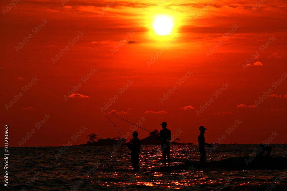 Silhouette of fishermans on the beach at sunset