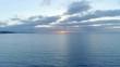 Forward flight over sea towards setting sun - tranquil scene