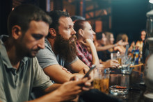 Bearded Man In Crowded Bar Watching Something