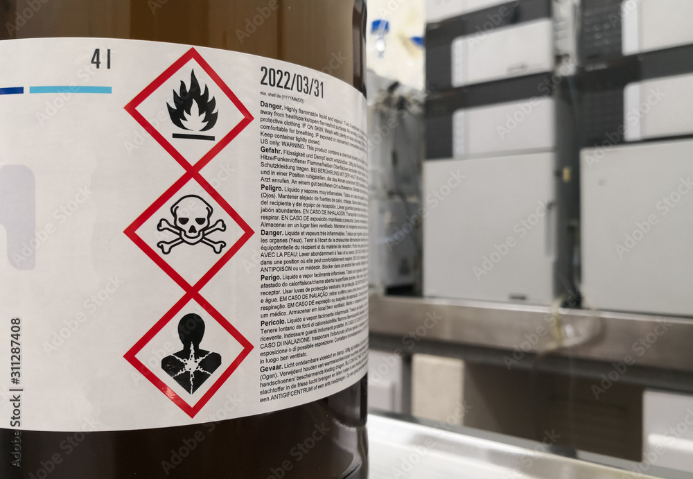 Fototapeta Chemical substance in a laboratory. Amber glass bottle. Tagged with GHS symblogy with toxicity, flammability and death warnings. Liquid chromatography equipment.