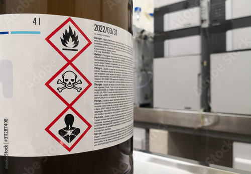 Chemical substance in a laboratory. Amber glass bottle. Tagged with GHS symblogy with toxicity, flammability and death warnings. Liquid chromatography equipment. - fototapety na wymiar
