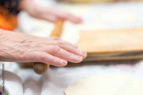 Fototapeta cook, female hand rolls the dough on a wooden board obraz na płótnie