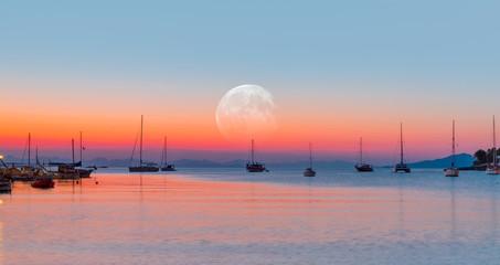 Fototapeta Wschód / zachód słońca Sailing yacht parked in Datca bay with full moon - Datca peninsula, Turkey at sunrise