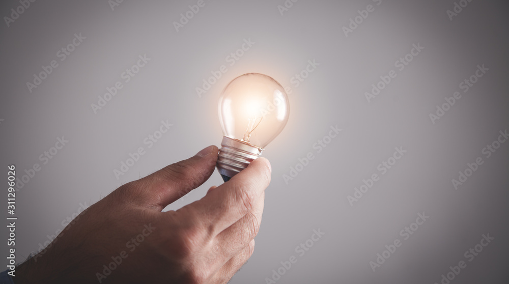 Fototapeta Hand holding light bulb. Inspiration, Creativity
