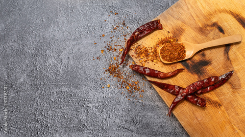 Cayenne pepper in a wooden spoon and dried chillies placed on a wooden chopping Canvas Print