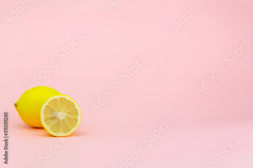 Yellow lemon and part of it on a pink background with place for text Poster Mural XXL
