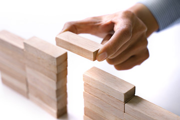 hand of people building up the wooden brick block bridge wall, Business risk and strategy concept.
