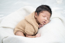 Happy Cute Adorable Asian Baby Boy With Black Hair Lying On A White Blanket.