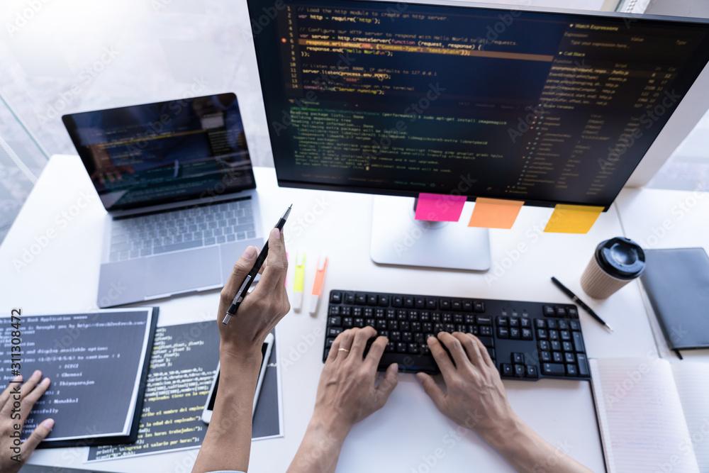 Fototapeta Pensive programmer working on on desktop pc programming code technologies or website design at office Software Development Company