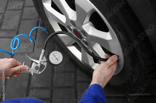 Fotografie, Obraz Mechanic checking tire air pressure at car service, closeup
