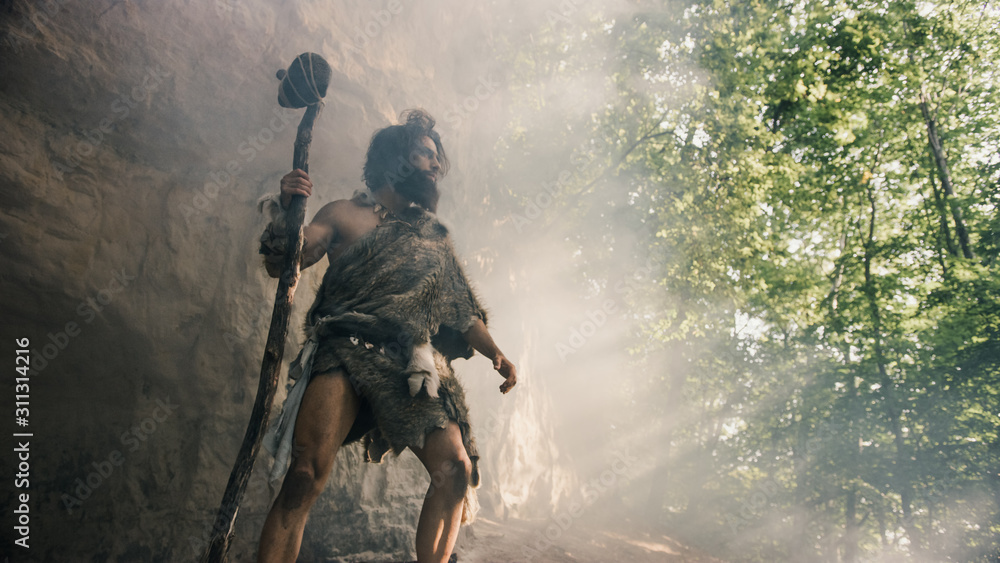 Fototapeta Primeval Caveman Wearing Animal Skin Holds Stone Hammer Stands Near Cave and Looks Around Prehistoric Landscape, Ready to Hunt Animal Prey. Neanderthal Going Hunting into Jungle. Low Angle Shot