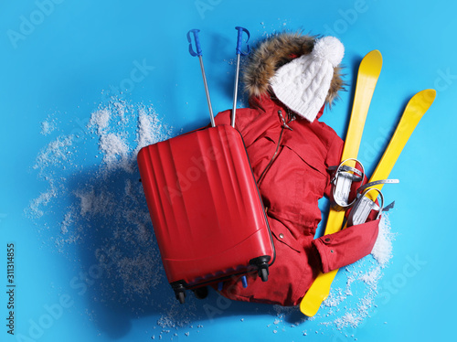 Fotomural Suitcase with warm clothes and skis on light blue background, flat lay