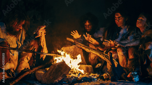 Fotografía Neanderthal or Homo Sapiens Family Cooking Animal Meat over Bonfire and then Eating it