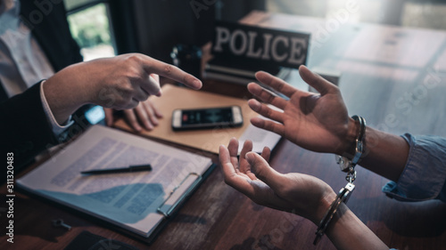 Police officer interrogating suspect or criminal man with handcuffs arrested at the investigation Canvas Print