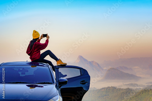 plakat young woman sitting on the car roof with enjoy taking photo with mobile phone to the nature of mist in the mountain at sunrise morning, cheerfully life travel