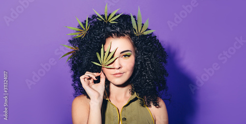 Mixed race woman with Afro-curls holding hemp Leaf Wallpaper Mural