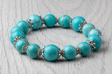 Bracelet Made Of Natural Turquoise Stone On A Light Wooden Background. Close-up