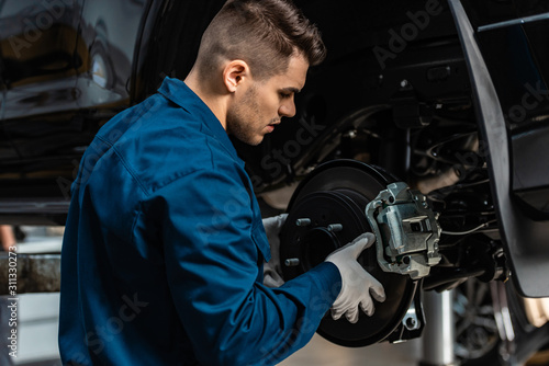 Cuadros en Lienzo young, attentive mechanic installing disc brakes on raised car