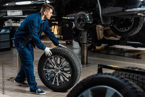 young mechanic holding car wheel near raised car in workshop Canvas Print