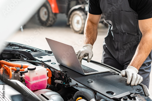 Fotomural cropped view of mechanic using laptop near car engine compartment